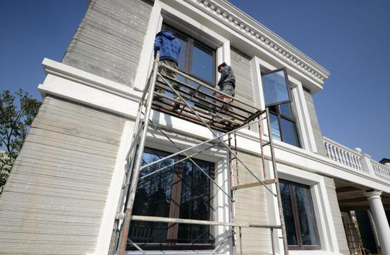 工人正在3D打印别墅外部进行施工 3D打印造价低墙体强度高,保温性能好 3D打印建筑最大的好处是节能环保、节省材料。因为3D打印建筑不产生任何扬尘和建筑垃圾。采用3D打印技术,可节约建筑材料30%到60%,工期缩短50%到70%。建筑成本可至少节省50%以上。并且顾客可以私人定制家居和房子风格。 因为墙体是由水泥、少量钢筋和一些建筑垃圾构成,不少人怀疑墙体的强度。对此,材料供应商表示,因为打印材料里面添加了一些特殊的助剂,所以3D打印出来的墙体的强度是普通墙体的5倍。此外,中间的空心空间里可以填充各种保